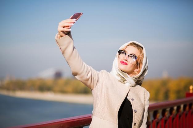 スマートフォンで自分撮りをしている素敵な若いモデル。女性はショールと眼鏡をかけています