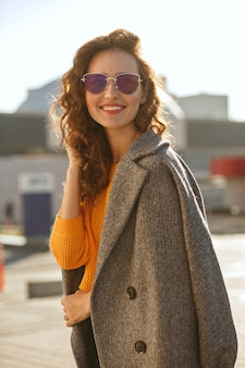 Lovely young model with curly hair in sunglasses wearing trendy outfit and walking down the sunny street