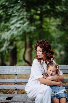 Прекрасная молодая мама и дочь в солнечный день в парке, счастливая семья