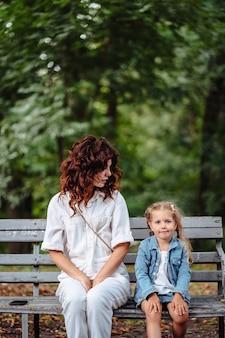 公園で晴れた日に素敵な若いママと娘、幸せな家族