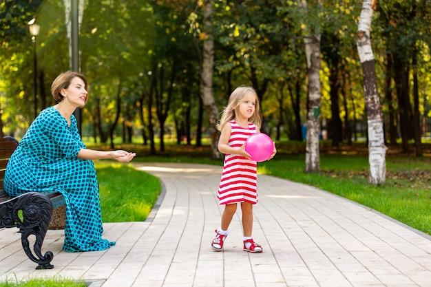 素敵な若いお母さんと娘の暖かい晴れた夏の日。幸せな家族の母と子小さな娘は風船で遊んで、公園を散歩して美しい自然を楽しんでいます。
