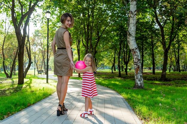 Прекрасная молодая мама и дочь в теплый солнечный летний день