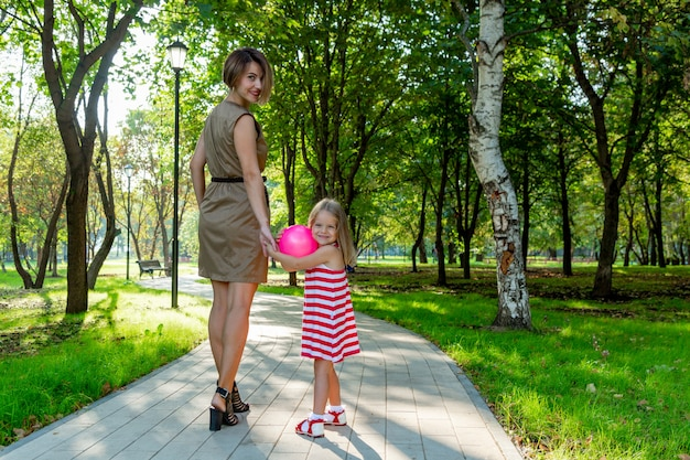 Lovely young mom and daughter in warm sunny summer day