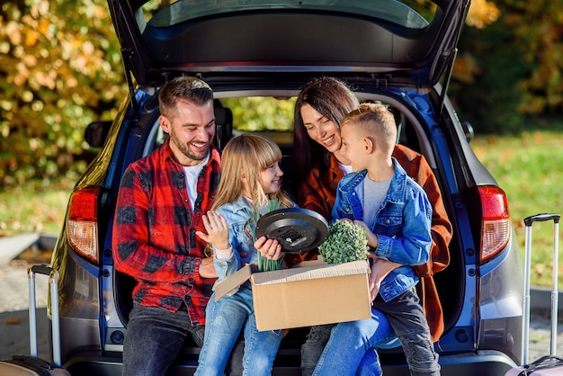 Lovely young parents with their cute kids sitting in the trunk and holding carton box with plants and other home things during moving into new apartment.