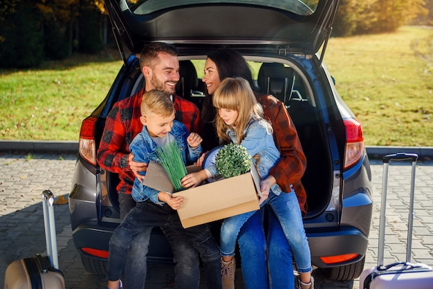 Lovely young parents with their cute kids sitting in the trunk and holding carton box with plants