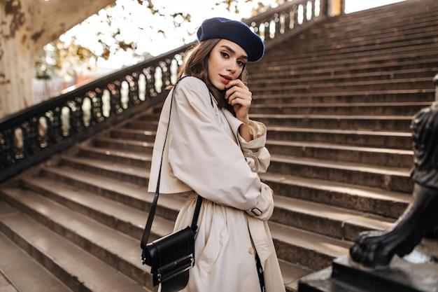 Bella giovane donna parigina con capelli castani in berretto elegante, trench beige e borsa nera, in piedi su vecchie scale e posa sensibile all'aperto