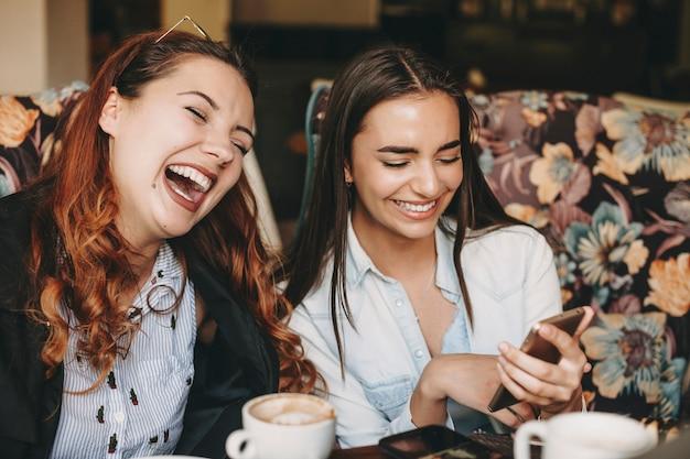 그녀의 여자 친구가 커피 숍에서 커피를 마시는 동안 그녀의 스마트 폰에 뭔가를 보여 주면서 사랑스러운 젊은 더하기 크기 여자는 닫힌 눈으로 웃고 재미 있습니다.