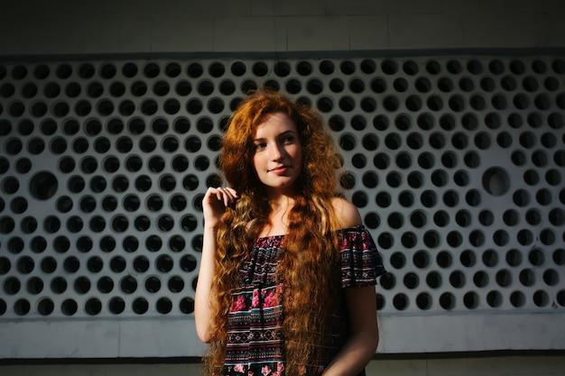 そばかすのある素敵な若い赤い髪のモデル。太陽の光でポーズをとって裸の肩を持つ女性