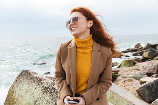 Прекрасная молодая рыжая женщина в осеннем пальто гуляет по пляжу, слушает музыку в наушниках
