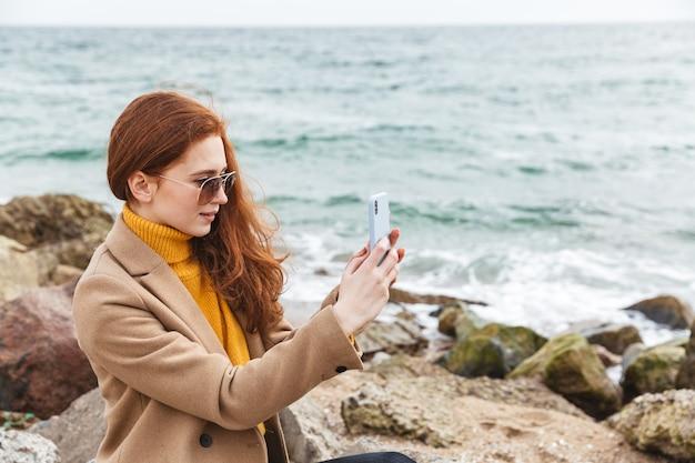 Прекрасная молодая рыжая женщина в осеннем пальто гуляет по пляжу, делая селфи