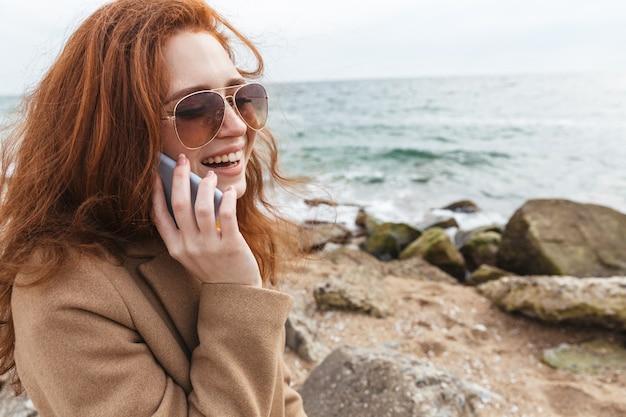 Прекрасная молодая рыжая женщина в осеннем пальто гуляет на пляже, разговаривает по мобильному телефону