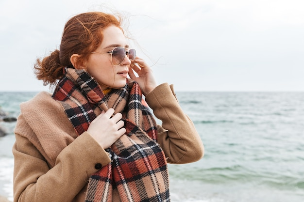 Lovely young redhead woman wearing autumn coat walking at the beach
