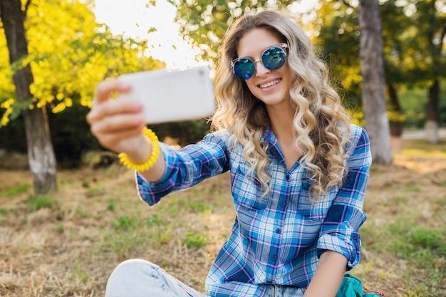 公園、夏のカジュアルスタイルに座っている素敵な若いスタイリッシュな魅力的な笑顔金髪女性