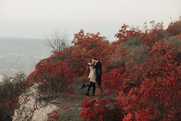 Прекрасная молодая стильная пара целуется и обнимается на открытом воздухе в осенней красочной природе