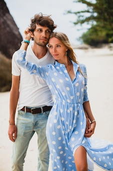 Lovely young stylish hipster couple in love on tropical beach during vacation