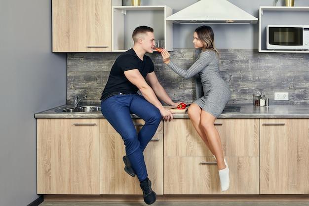 Милая молодая белая женщина сидит на индукционной плите, встроенной в кухонный стол, и кормит привлекательного мужчину сладким перцем.