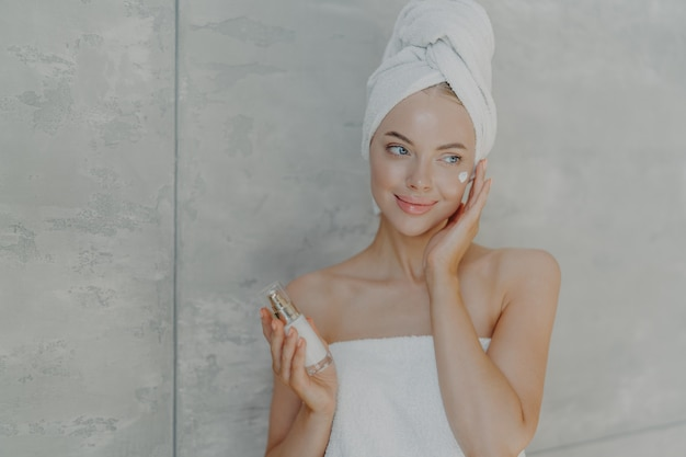 Lovely young woman applies beauty lotion on face has satisfied expression wears bath towel on head