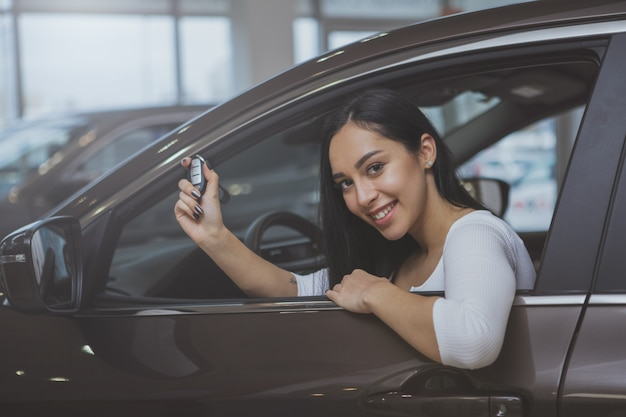 Lovely young woman buying new car at the dealership