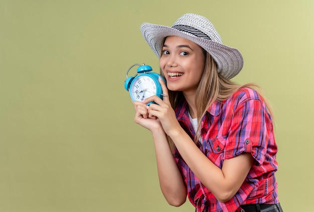 A lovely young woman in a checked shirt holding blue alarm clock