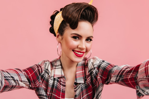 Lovely young woman in checkered shirt smiling on pink background. emotional pinup girl taking selfie.