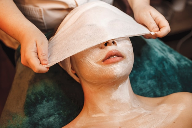 Lovely young woman doing facial skin care procedures in a spa center.