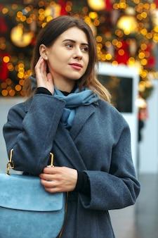 겨울에 거리를 걷고 있는 트렌디한 코트를 입은 사랑스러운 젊은 여성