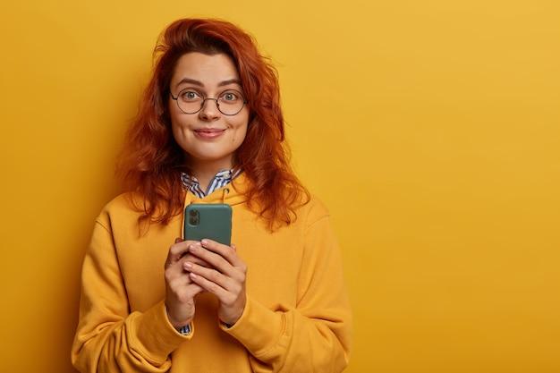 素敵な若い女性は生姜髪をしていて、メッセージを送信したり、ソーシャルネットワークをサーフィンしたりするための携帯電話を持っており、スウェットシャツ、丸いメガネをかけています