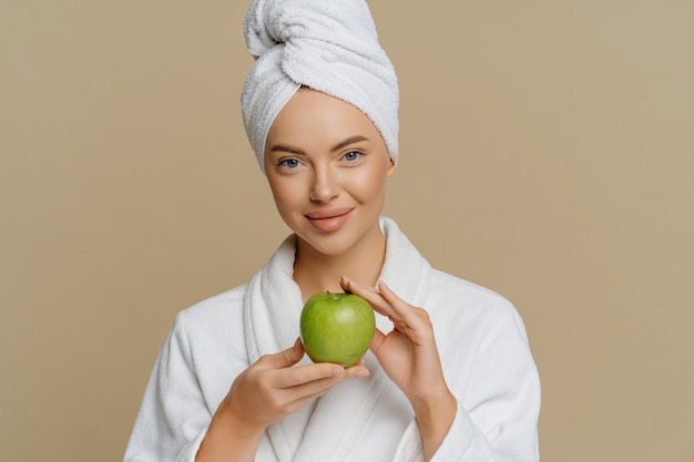 Lovely young woman has refreshed skin after taking bath dressed in dressing gown wrapped towel on head holds green apple