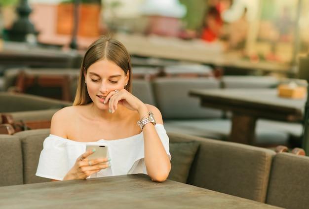 ストリートカフェのテーブルに座ってスマートフォンを手に持っている素敵な若い女性