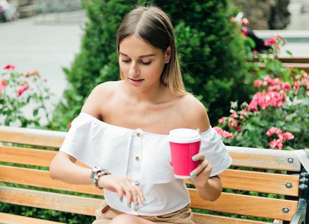 Милая молодая женщина держит чашку кофе и смотрит на наручные часы, сидя на скамейке в парке