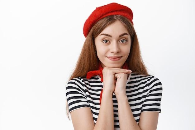 赤いベレー帽をかぶった素敵な若い女性、正面を見つめ、笑顔であなたを賞賛と興味を持って見て、白い壁の上に立っています