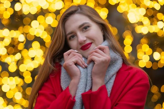 ストリートフェアで歩く赤いコートを着た素敵な若い女性