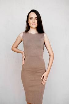 タイトなニットドレス、長いストレートの黒い髪、ハイヒールの靴がスタジオでポーズをとって素敵な若い女性
