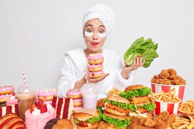 사랑스러운 젊은 여성이 입술을 핥고 녹지 대신 먹고 싶은 맛있는 달콤한 도넛을 들고 있습니다