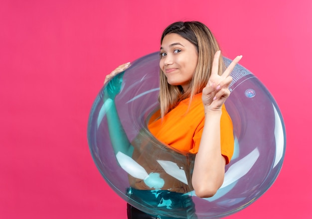 A lovely young woman in an orange t-shirt showing two fingers gesture while standing on inflatable ring on a pink wall
