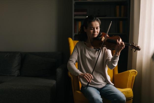 Прекрасная молодая женщина играет на скрипке, сидя на мягком стуле в комнате с современным интерьером. девушка занимается игрой на музыкальном инструменте дома.