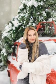 雪の降る天気でレトロな赤い車の近くでポーズをとって素敵な若い女性