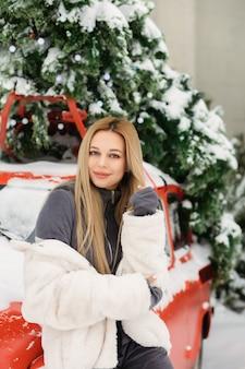 Прекрасная молодая женщина позирует возле ретро красной машины зимой