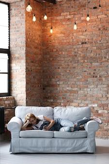 Прекрасная молодая женщина отдыхает на диване, интерьер гостиной