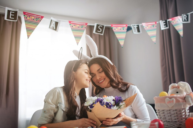 Lovely young woman sit together with daughter in room and prepare for easter. model hold bouquet of flowers. daughter kiss mother. nice and cute.