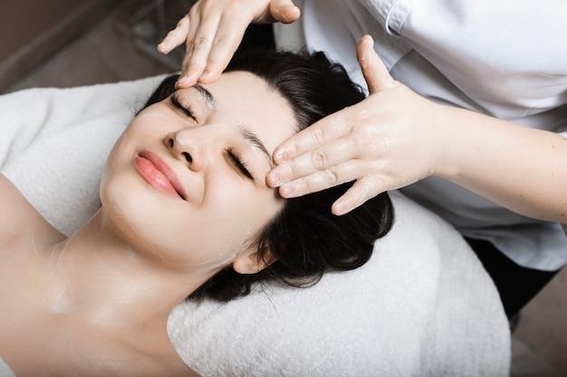 Прекрасная молодая женщина улыбается во время массажа лица в спа-центре.