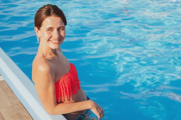사랑스러운 젊은 여자가 해변, 복사 공간이 수영장에서 물에 서. 그녀의 여름 휴가 동안 일광욕 행복 한 아름 다운 여자. 리조트, 호텔 컨셉