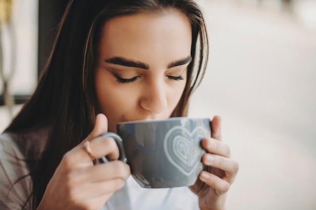 카페에서 수업 후 커피 한 잔을 마시는 사랑스러운 젊은 여자 학생. 커피를 마시는 아름 다운 여자 닫습니다.