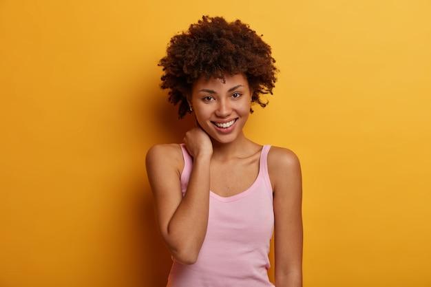 Милая молодая женщина трогает шею, смотрит с нежной улыбкой, чувствует себя хорошо и тронута, носит повседневную футболку, смотрит прямо на желтую стену. положительные выражения человеческого лица