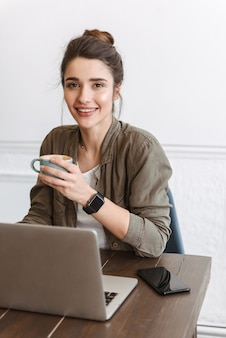 Lovely young woman using laptop computer while sitting indoors, drinking coffee