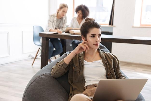 Прекрасная молодая женщина с помощью портативного компьютера, сидя в помещении, сидя в кресле
