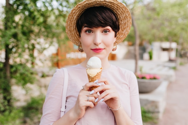 Lovely young woman in vintage outfit with elegant manicure walking on the street and eating vanilla ice cream with pleasure