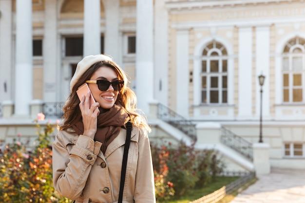 屋外を歩いて、携帯電話で話しているコートを着ている素敵な若い女性