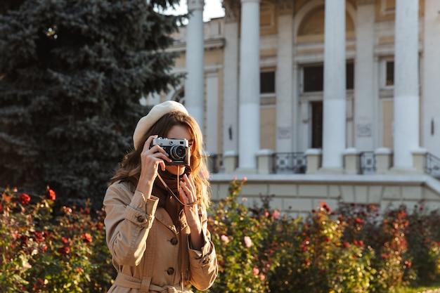 사진 카메라를 사용하여 야외에서 산책하는 코트를 입고 사랑스러운 젊은 여자
