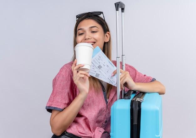 Una bella giovane donna che indossa una camicia rossa e occhiali da sole guardando una tazza di caffè di plastica mentre si tiene i biglietti aerei e la valigia blu su un muro bianco